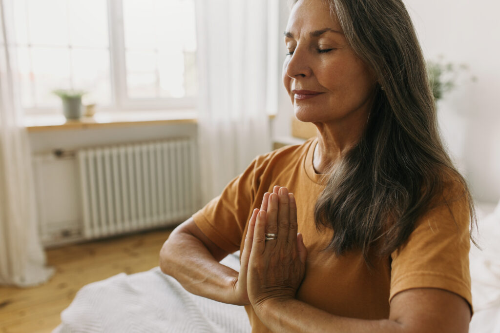 Calm middle-aged woman sitting in padmasana with eyes closed. Mature female holding hands pressed together in namaste and doing breathing exercises. Meditation and yoga idea
