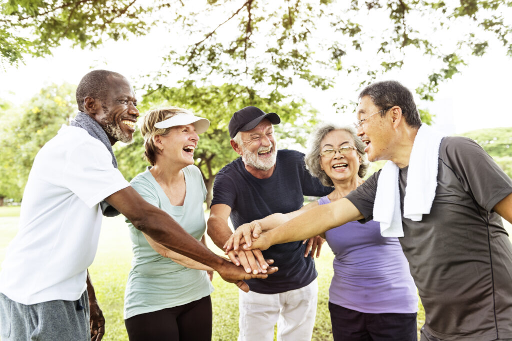 Diverse group of five smiling older adults in workout clothes standing in a half circle in a park with their hands stacked in the center of the group